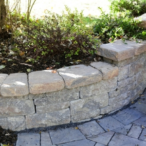 A curving, stone-texture Belgard Brookshire retaining wall beside a paver driveway in Ulster County, NY, by Masseo Landscape, Inc.