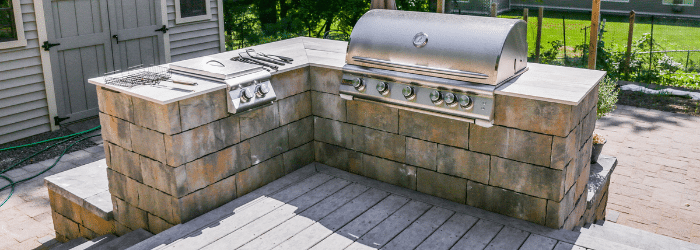 A chrome grill and side burgers set into a Belgard precast concrete wall wrapping around the corner of a deck in a backyard in New Paltz, NY