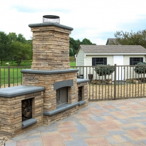 A Belgard Bordeaux series outdoor free standing fireplace with side wood boxes on a Belgard patio with pool fencing.