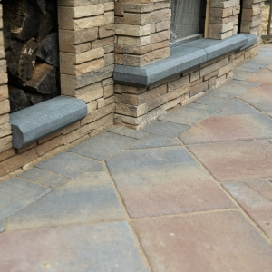 A detail showing the Belgard precast concrete paver patio with a contrasting border cut to fit around the base of a precast concrete fireplace.