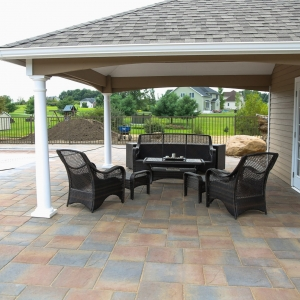 Patio furniture beneath the awning of a tan pool house on a Belgard paver patio with tan, brown, and gray toned pavers.