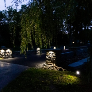 A driveway flanked by two precast concrete walls with pillars with lights on them in Gardiner, NY.