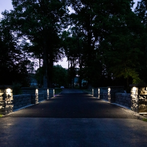 A head-on view of a driveway at night with two precast concrete stone texture retaining walls with pillars on either side. The scene is lit by outdoor lighting installed on each pillar. Designed and installed by Masseo Landscape, Inc, New Paltz Landscapers.