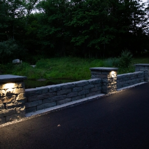 A precast concrete Rosetta Kodah retaining wall with pillars along a driveway. Each pillar has a cap and is lit with an undercap outdoor lighting fixture.