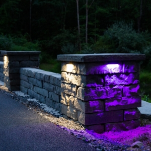 A purple light illuminates a stone-texture precast concrete pillar set into a free standing wall along a driveway. Alliance color-changing LED outdoor lighting and Rosetta Kodah wall installed by Masseo Landscape, Inc.