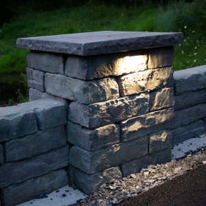 A detail of a pillar set into a free standing wall baring and outdoor lighting fixture set under its cap. Rosetta Kodah precast concrete pillar and wall designed and installed by Masseo Landscape, Inc. in Gardiner, NY