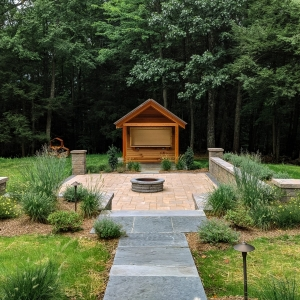 A wooden bar shed with an overhang behind a tan precast concrete Belgard paver patio with a round fire pit. A bluestone walkway, native plantings, and outdoor lighting fixtures are in the foreground. Designed and installed by Ulster County Landscapers, Masseo Landscape, Inc.