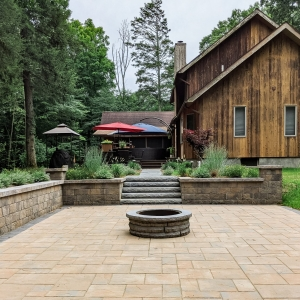 A tan precast concrete paver patio, retaining walls, and steps with a circular fire pit and contrasting paver border next to a wooden house in Stone Ridge, NY by Masseo Landscape, Inc.
