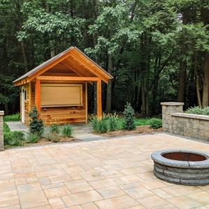 A wooden bar shed next to a precast concrete patio with pillars and a retaining wall and a circular firepit, installed by Masseo Landscape, in Stone Ridge, NY