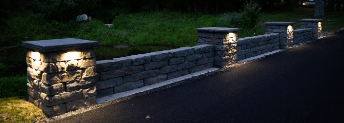 Niche lighting on a precast concrete wall with pillars. Landscape Lighting installed by Masseo Landscape, Inc.