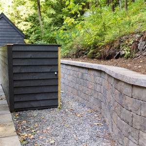 A Belgard Lafitt Tandem precast concrete stone texture retaining wall, stone walkway, and wooden utility screening wall in Woodstock, NY.