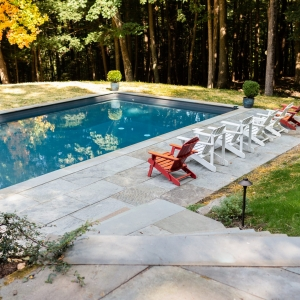 A pool with a bluestone patio and colorful chairs in the sunlight in Woodstock, NY.