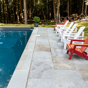 A geometric cut bluestone patio next to a pool with matching bluestone coping and colorful Adirondak chairs in Woodstock, NY.