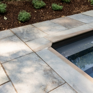 A detail highlighting geometric cut bluestone patio with natural color bluestone coping on a pool corner.