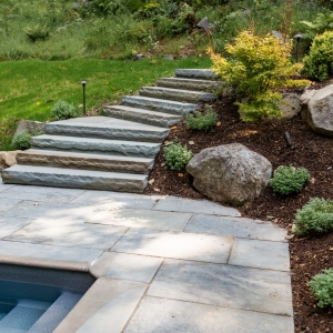 Stone face bluestone staircase set into a hillside with catmint and Japanese maple plantings set with natural boulders and landscape lighting next to a bluestone pool patio in Woodstock, NY.
