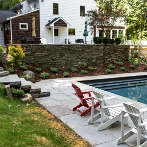 A pool with a bluestone patio and bluestone coping with split face steps to a higher patio and planting spaces planted with native plants in Woodstock, NY.