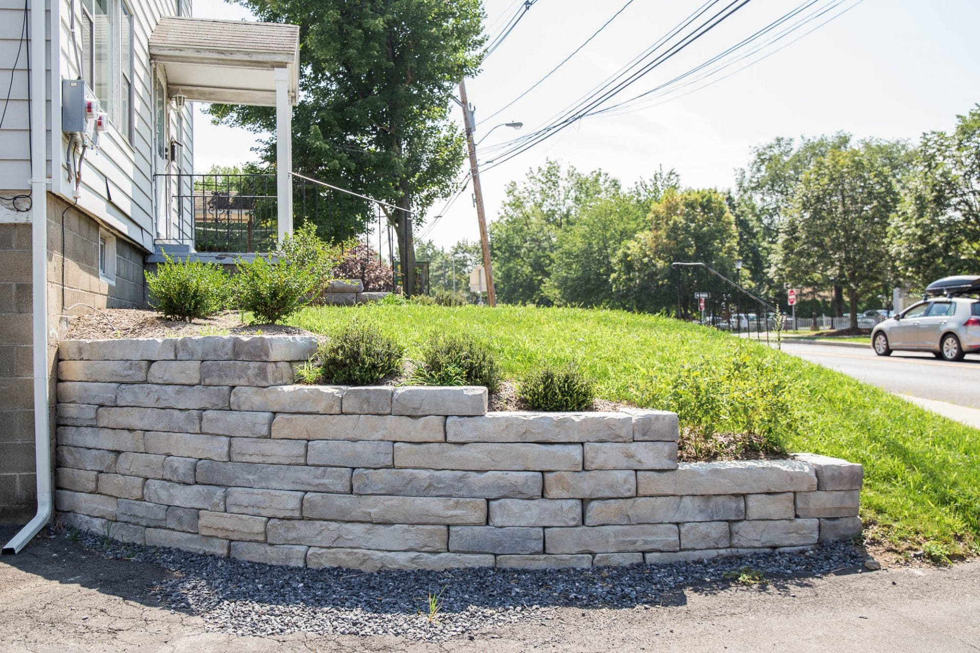 A curved retaining wall built from stone texture Kodah wall stone by Rosetta Hardscapes.