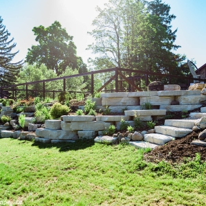 A retaining wall and steps constructed from precast concrete and natural stone in High Falls, NY.