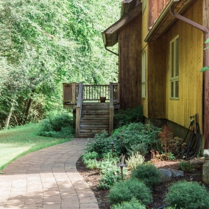 A curving paver walkway to a front wooden entry with native plantings alongside of a house in Ulster County, NY