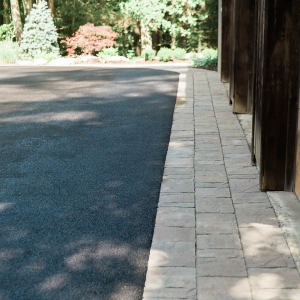 A band of Belgard precast concrete pavers along a driveway garage entrance in Cottekill, NY, installed by Ulster County Landscaper Masseo Landscape, Inc.