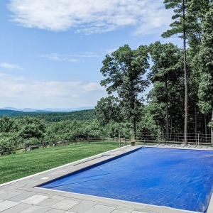 A rectilinear bluestone patio surrounding a pool in New Paltz, NY