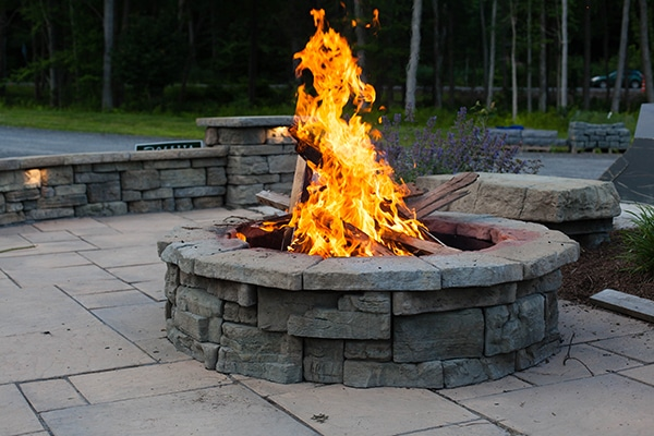 Stone fire pit with blazing fire.