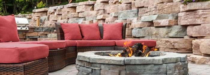 Image of outdoor fire pit with couch and retaining wall in background.