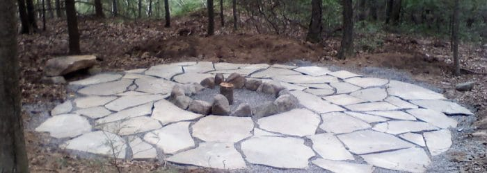Natural bluestone fire pit set in woods.