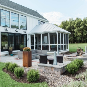 A geometric bluestone patio built outside a screened porch on a modern farmhouse with brick inlay details, precast concrete seating walls, native landscape plantings, and a precast concrete fire pit in Gardiner, NY, installed by Masseo Landscape, Inc.