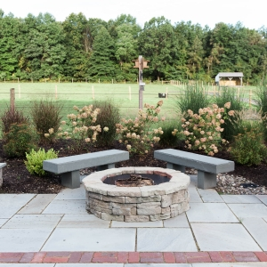 A circular precast concrete fire pit and bluestone slab benches on a rectilinear bluestone patio with native plants like hydrangea and spirea behind, installed by Masseo Landscape, Inc. Hudson Valley Landscaper