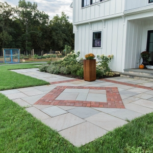 A geometric cut bluestone entryway landing with a diamond-shaped recycled brick inlay and metal planters in front of a modern farmhouse in Gardiner, NY, designed and installed by Masseo Landscape, Inc., Gardiner Landscapers