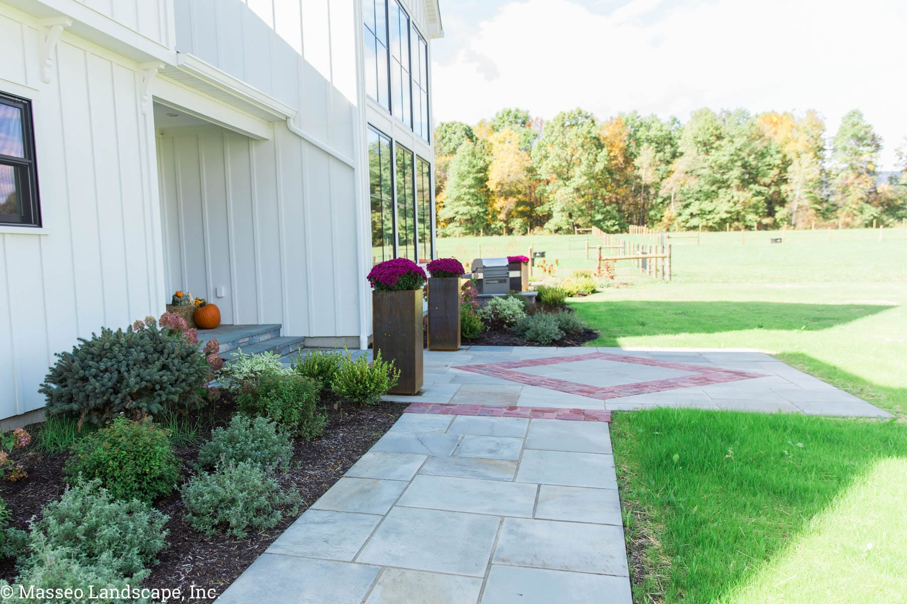 A bluestone walkway and landing with brick inset designs installed by Masseo Landscape, Inc., Gardiner Landscapers