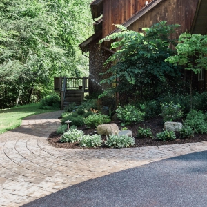 A curving paver front entry path with planting beds and outdoor lighting on either side with built-in irrigation in Cottekill, NY, designed and installed by Hudson Valley Landscaper Masseo Landscape, Inc.