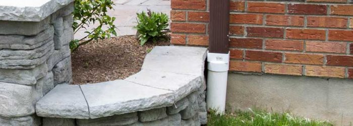 Gutter drain tied into underground drainage - Landscape drainage contractor services.
