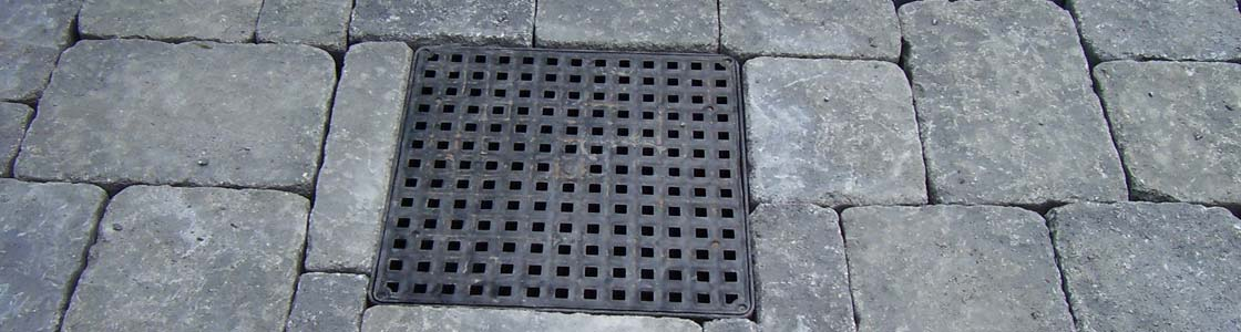 Drainage grate inset in stone patio.