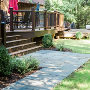 A geometric bluestone landing patio with plantings at base of back yard deck steps in Ulster County, NY, installed by Masseo Landscape, Inc.