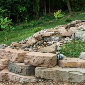 A custom water feature built with a blend of precast concrete and natural stone, with ambient outdoor lighting, installed and designed by Masseo Landscape, Inc.`