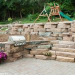 An outdoor kitchen area featuring Rosette Hardscapes wall stone.