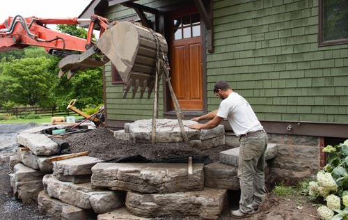 Image of Masseo Landscape staffer placing stone with backhoe - High Falls Project.