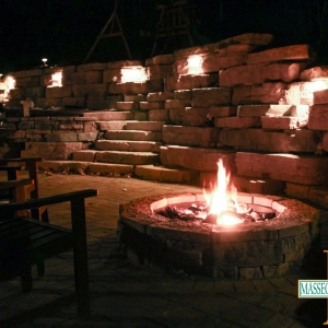 A fire pit and lighting fixtures illuminate a rustic patio and steps at night.