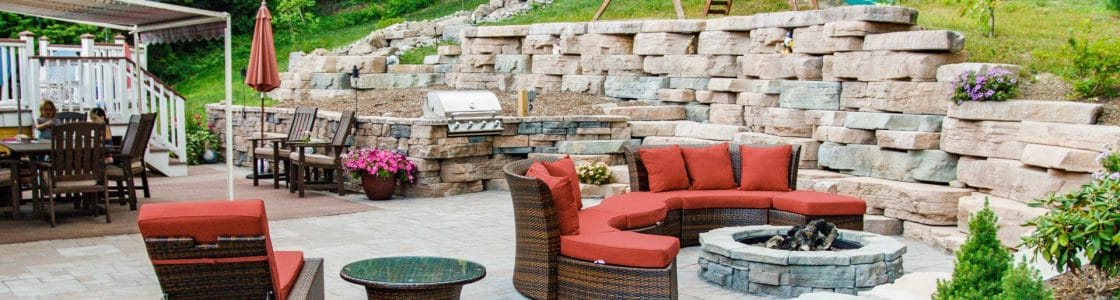 Patio with fire pit, seating and outdoor kitchen installed by outdoor living contractor, Masseo Landscape