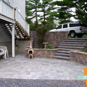 A semi-circular patio with a tiered retaining wall and steps.