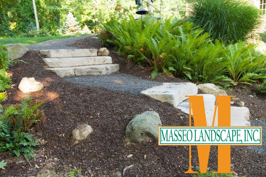 Rustic pre-cast concrete steps with a gravel walkway in a mulched planting.