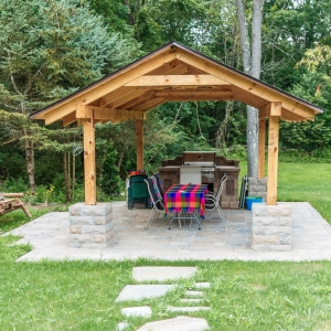 A wooden pavilion with a precast concrete patio and outdoor kitchen.