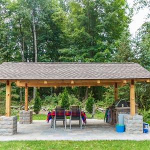 A precast concrete Belgard patio and outdoor kitchen beneath a wooden pavilion.