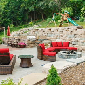 An outdoor living area with a Cambridge Pavers patio, retaining walls built from Rosetta Hardscapes wall stone, a circular fire pit, grill station, and built in seating.
