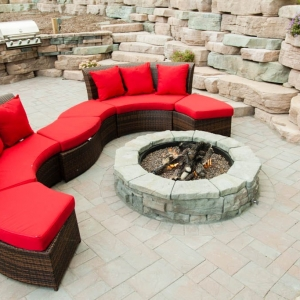 A circular Rosetta fire pit on a Cambridge Pavers patio.