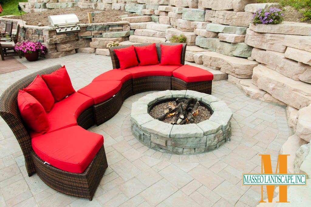 A circular Rosetta fire pit on a Cambridge Pavers patio.