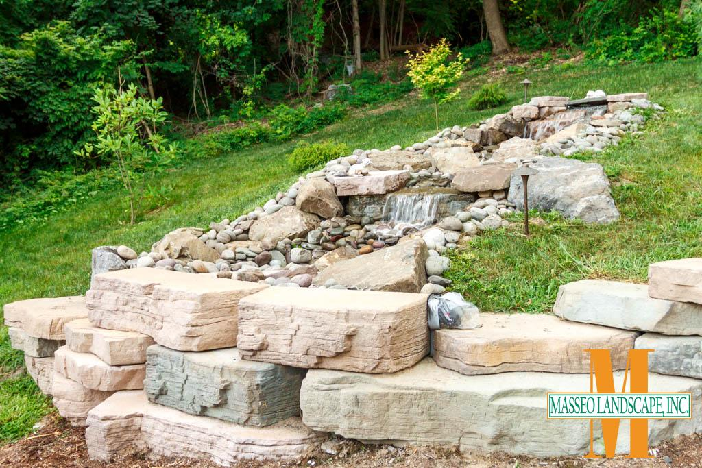 A custom built recylcing waterfall feature with CAST Lighting fixtures, built with Rosetta Outcropping and natural river rock.