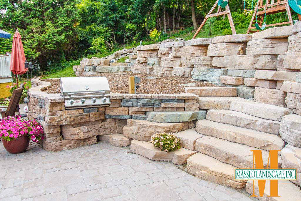 A grill station set into a Rosetta Belvedere retaining wall, which blends to a larger Outcropping retaining wall and Irregular steps.